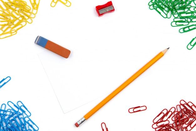 Карандаш, ластик, точилка, скрепки лежат под разными углами листа на белом фоне. изображение героя и копирование пространства. Premium Фотографии
