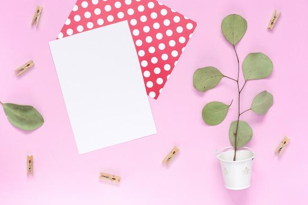 Веточка с листьями в белом ведре на простом розовом фоне копией пространства Premium Фотографии