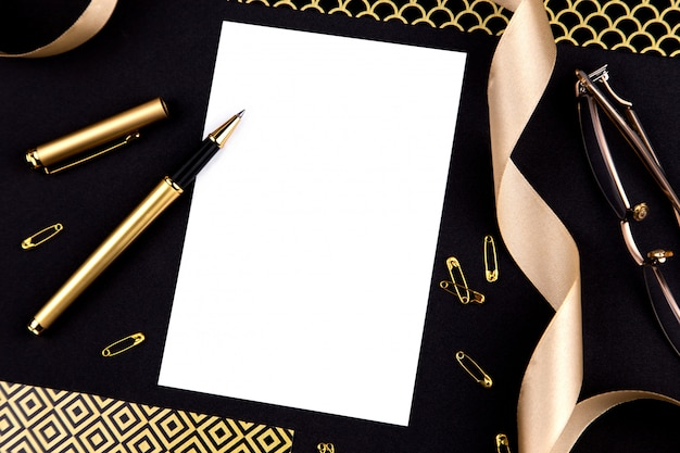 Золотая ручка, лента, скрепки и канцелярские товары на черном фоне с белым листом бумаги с копией пространства Premium Фотографии