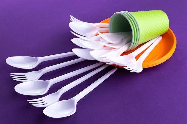 紫色の使い捨てのプラスチック製食器類の明るいオレンジとグリーンのセット Premium写真