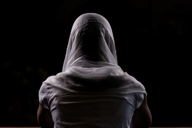 教会に座っていると祈っている若い女の子のシルエット Premium写真