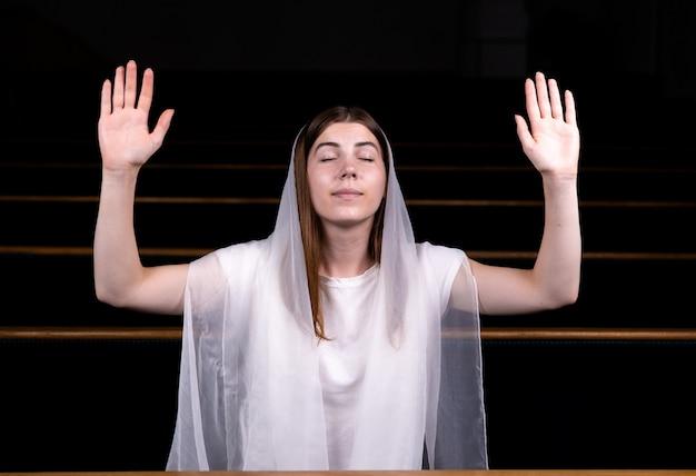 Молодая скромная девушка с платком на голове сидит в церкви и молится. Premium Фотографии