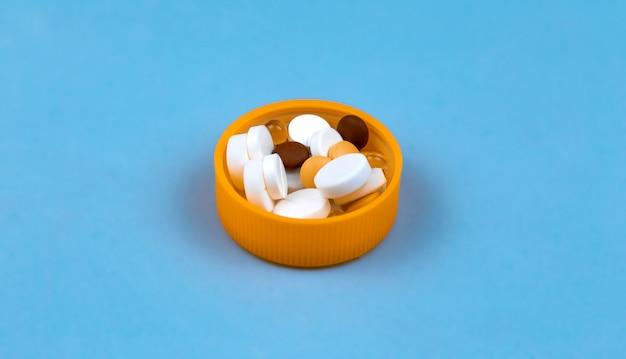 錠剤のパッケージのキャップにある着色された錠剤の用量。青色の背景に Premium写真