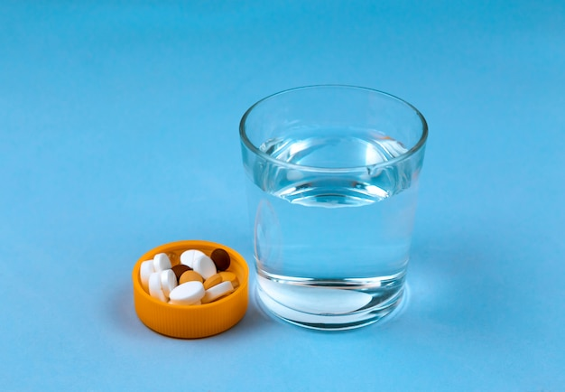 Стакан воды и таблетки на синем фоне Premium Фотографии