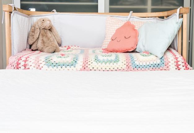 子供とおもちゃのためのクッション付きのベビーベッド。 Premium写真