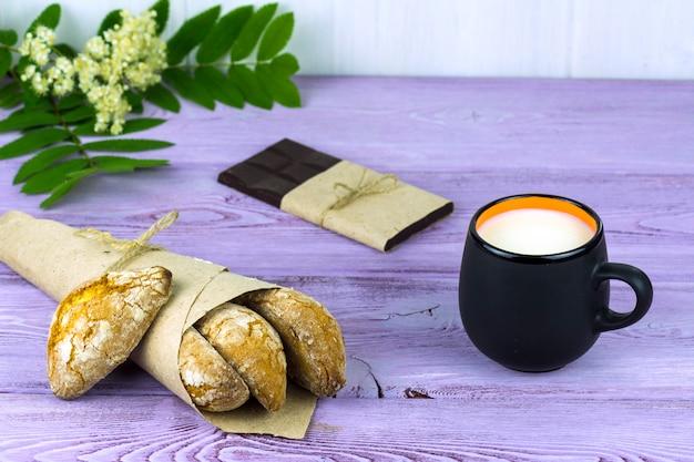 テーブルの上に、春の花、牛乳と自家製クッキーとチョコレートのマグカップ Premium写真