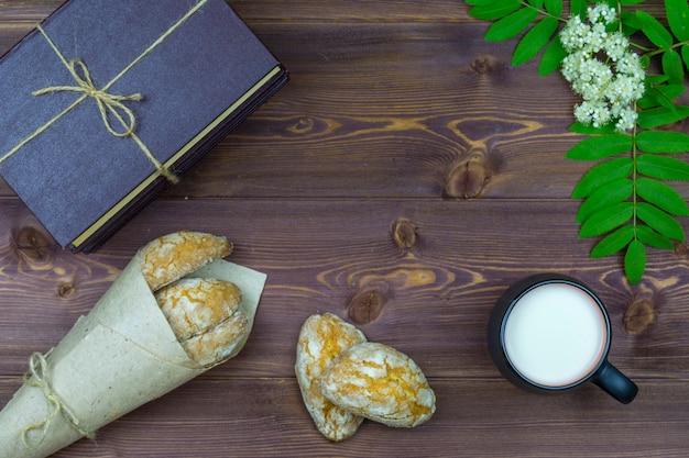 平置き。テーブルの上に、春の花、牛乳と甘い自家製クッキーや本のマグカップ。 Premium写真