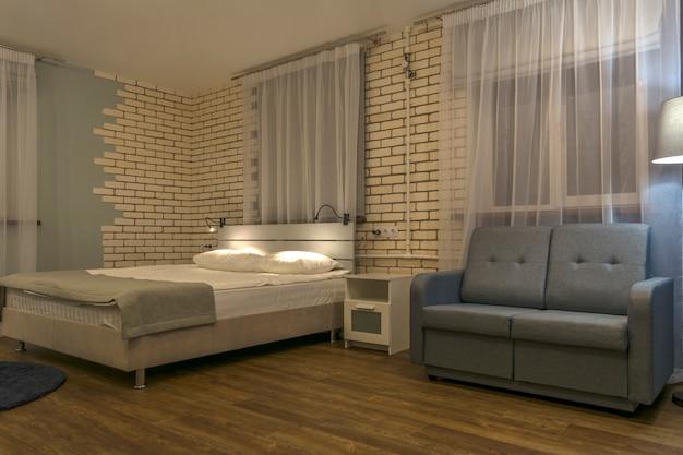 ベッドルームのインテリア、ダブルベッド、ソファ、大きな窓。 Premium写真