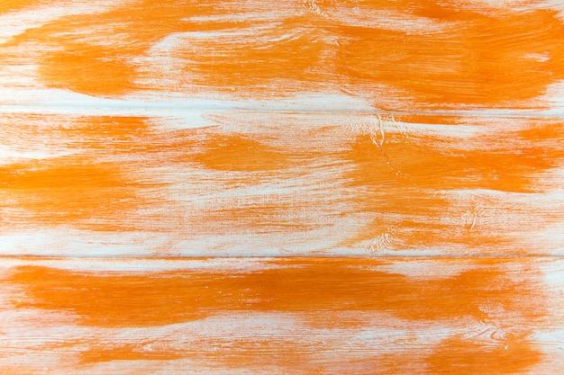 木の表面は白とオレンジ色で何度も再塗装されています。 Premium写真