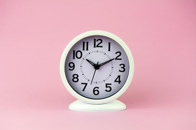 ピンクの背景に大きな数字の白い目覚まし時計。 Premium写真