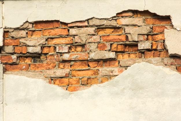 部分的に破壊された石膏、背景またはテクスチャを有するレンガ壁 Premium写真