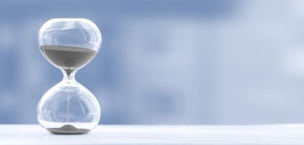 トレンディな青色の背景をぼかし、時間とガラスの砂時計 Premium写真
