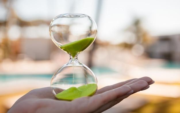 ガラスフラスコ-ぼやけて明るい背景に女の子の手で砂時計を流れる砂 Premium写真