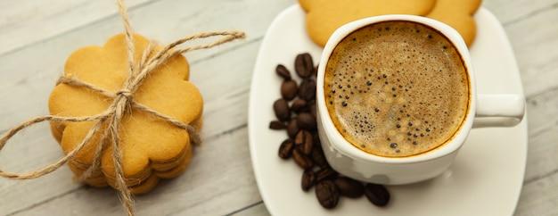 木製の背景、生姜クッキー、朝の良い気分にミルクの泡とブラックコーヒー Premium写真