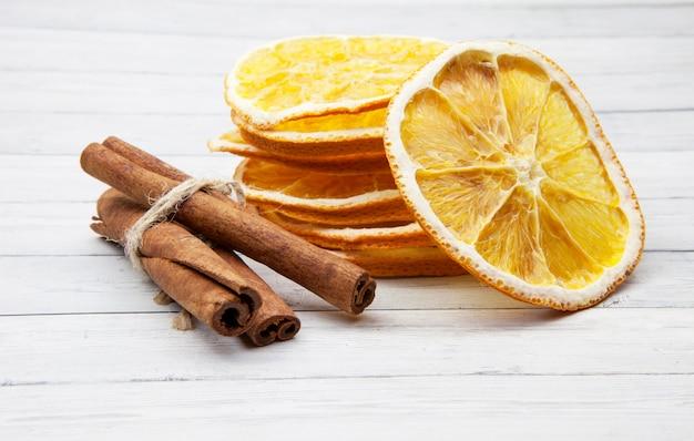 Апельсиновые дольки с корицей на светлом деревянном фоне, наслаждаясь специями Premium Фотографии