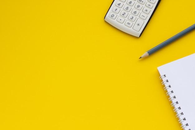 電卓、メモ帳、鉛筆、黄色の背景、テキストのスペース Premium写真