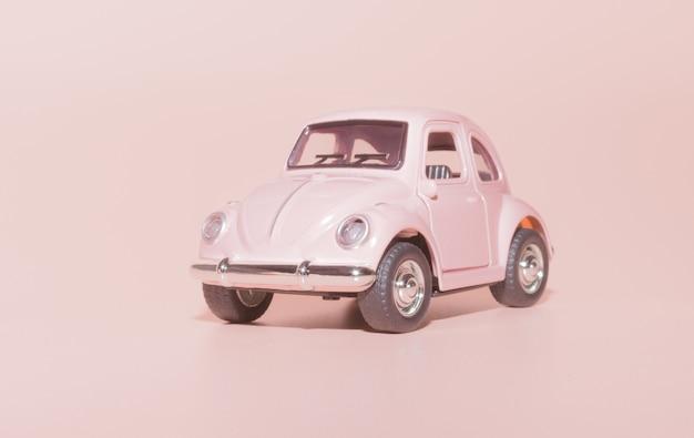 ピンクの背景にピンクのおもちゃレトロ車クローズアップ Premium写真