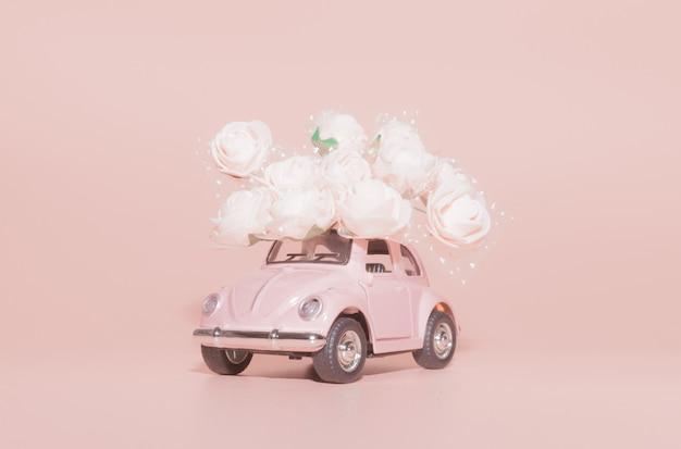 ピンクの背景に白のバラの花束とピンクのレトロなおもちゃの車。 Premium写真