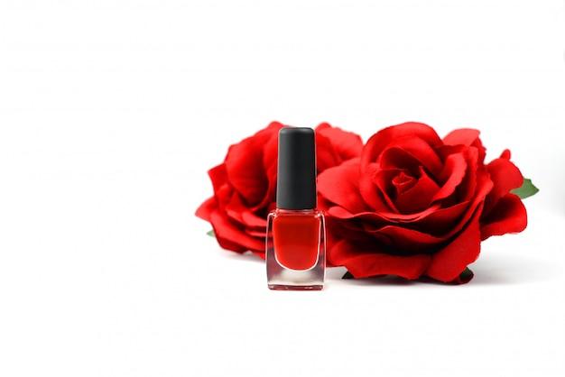白い背景の上の花のバラとマニキュア赤化粧品 Premium写真