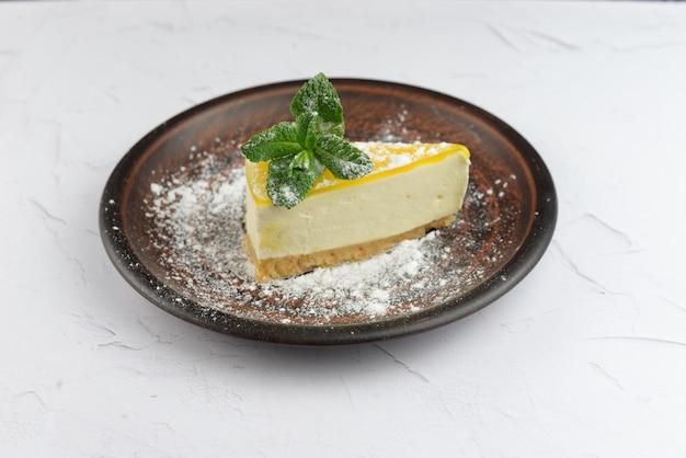 白い背景の上のミントの葉とレモンデザートケーキマスカルポーネチーズケーキ Premium写真