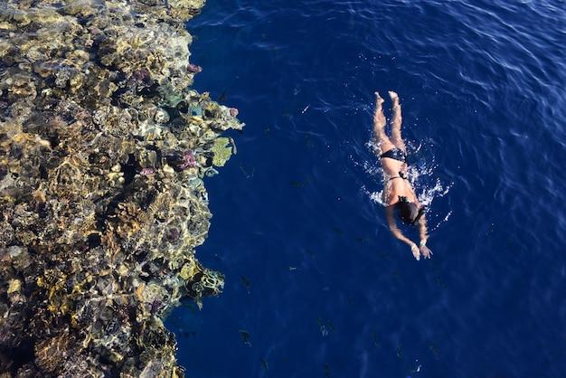 女の子は海でシュノーケリングで泳ぐ Premium写真