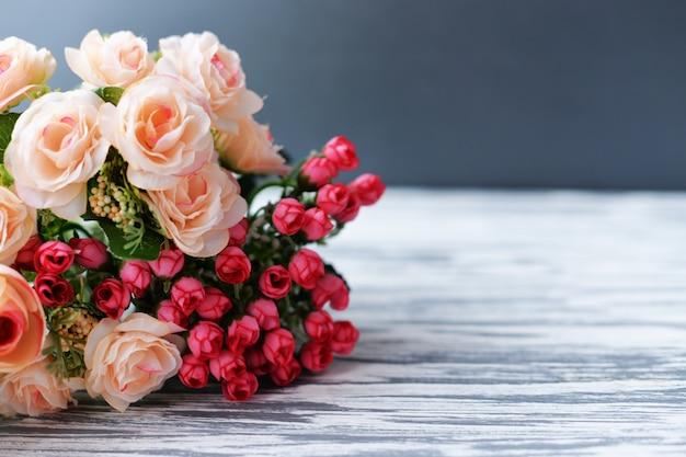 バラとバレンタインデーのための木製の背景にラベンダーからの花の花束 Premium写真