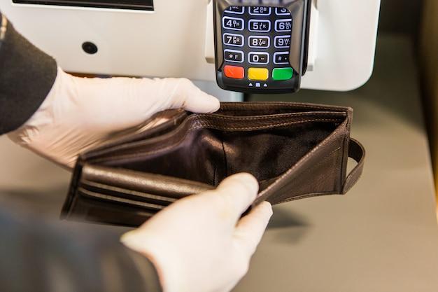 空の財布を保持している白いラテックス手袋の男。お金のない茶色の財布。財政問題 Premium写真