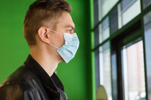 医療マスクの若い男。検疫セキュリティ。お店の男 Premium写真