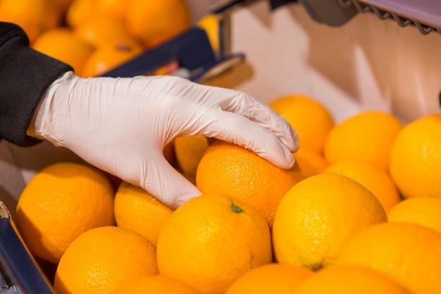 店で白い手袋をした男性が食べ物を買います。男は手にオレンジを持っています Premium写真