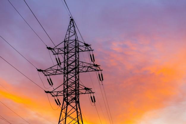 日没時の電力線のシルエット。明るいオレンジの都市の夕日 Premium写真