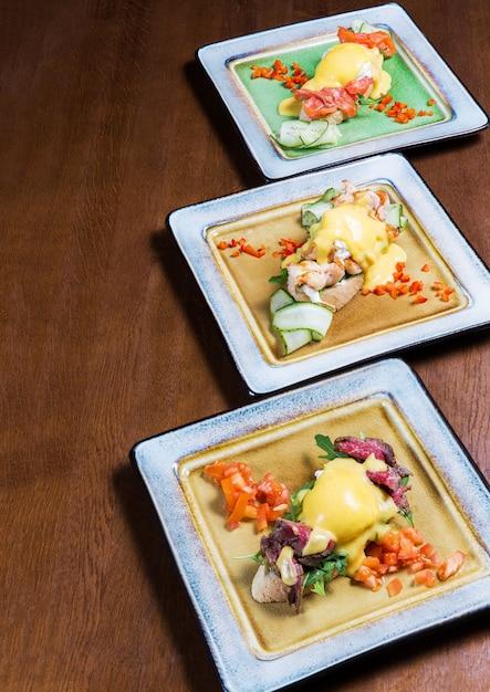 Вкусные утренние бутерброды с овощами, сыром и мясом в тарелках на деревянный стол в ар Premium Фотографии