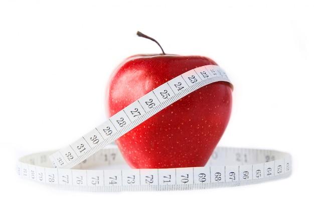 白い背景にセンチメートルと赤いリンゴ。白で隔離されています。健康的な食事 Premium写真