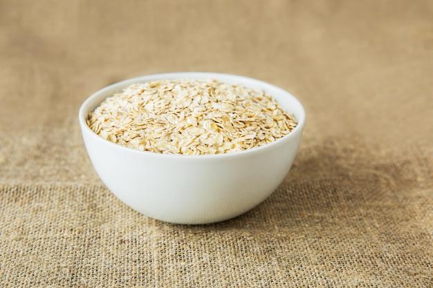 明るい茶色の繊維の背景に白いボールでオートミール。健康的な食事 Premium写真