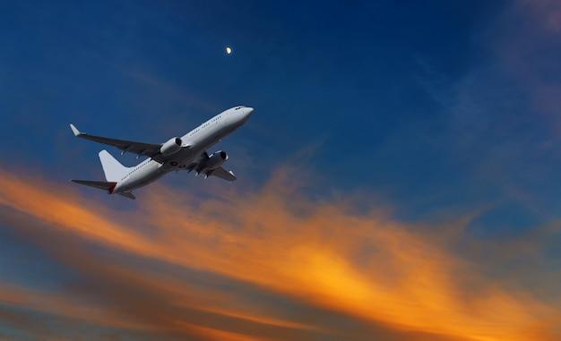 日没のオレンジと黄色で離陸後の商業飛行機の登山 Premium写真