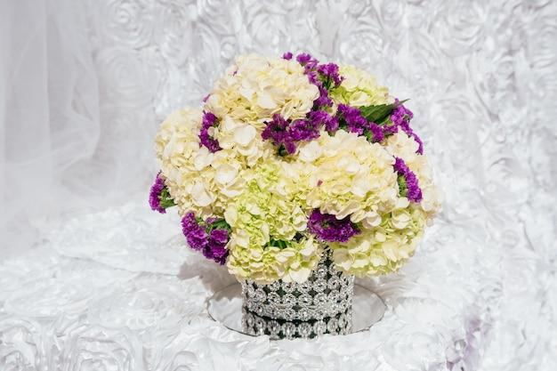 レストランの結婚式の花とテーブルのお祝い結婚式のテーブルの上のバラの花束 Premium写真