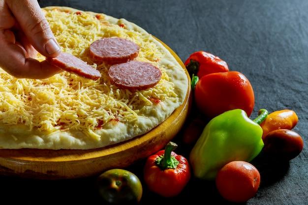 ピザのソーセージに材料を置くベイカーの手 Premium写真
