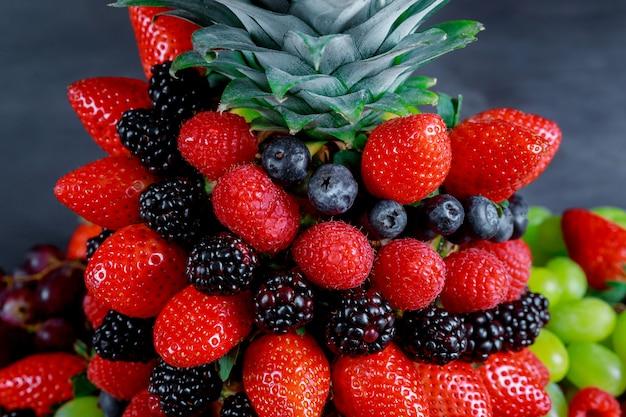 虹色、パイナップル、ブラックベリー、ブルーベリーの健康的な果実の表示 Premium写真