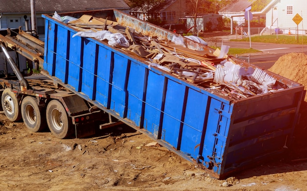 岩とコンクリートの瓦礫でいっぱいの青い建設ゴミ容器 Premium写真