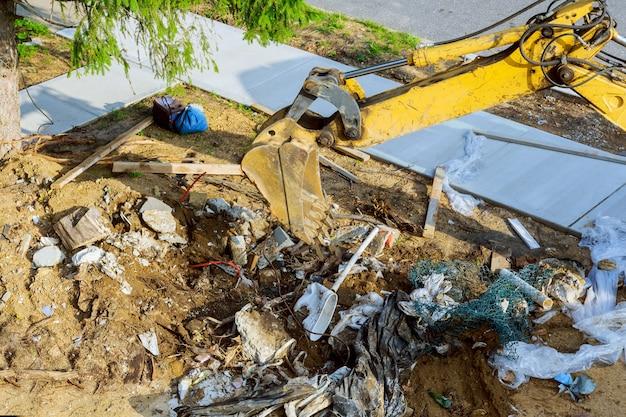 土壌汚染におけるゴミ捨て場に取り組むバックホー Premium写真