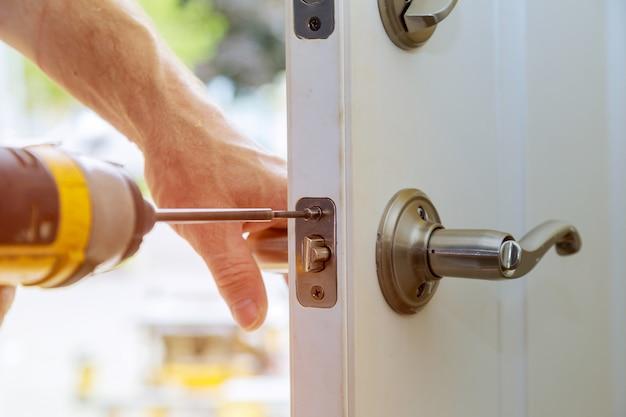取り付けは室内ドアのノブをロックし、クローズアップの木工師の手はロックを取り付けます。 Premium写真