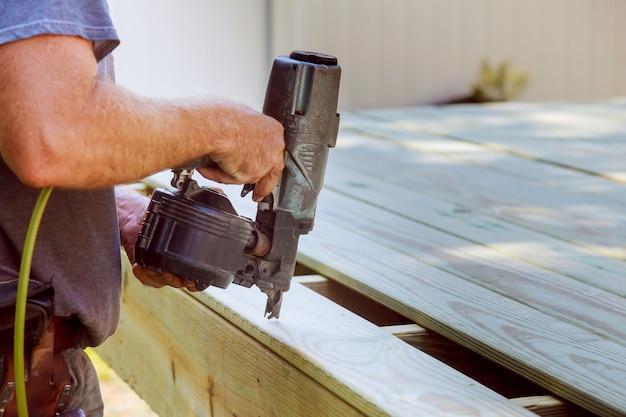 Красавец плотник установка деревянный пол на открытой террасе в новом доме Premium Фотографии