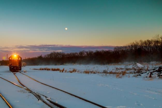 貨物列車は雪に覆われた広大な広がりを走ります Premium写真