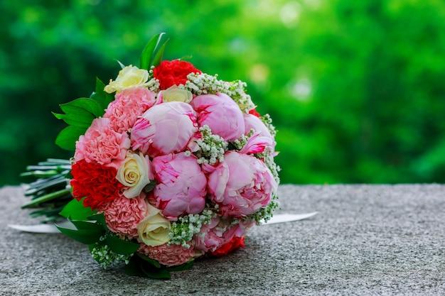 白い蘭の花、デイジーと赤い果実のウェディングブライダルブーケ Premium写真