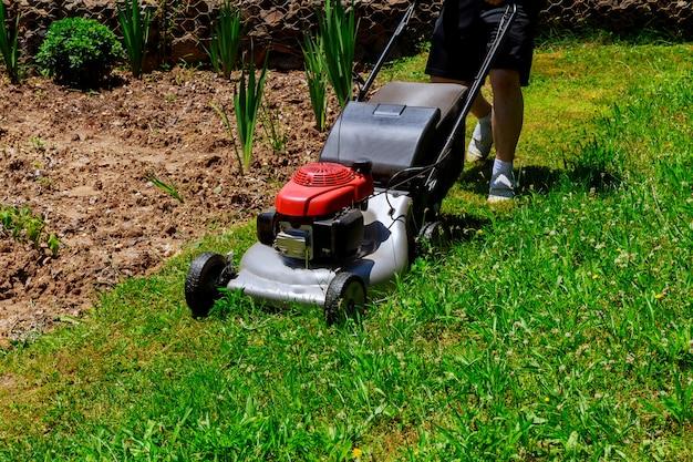 草刈り用の庭師によって使用されている芝刈り機 Premium写真