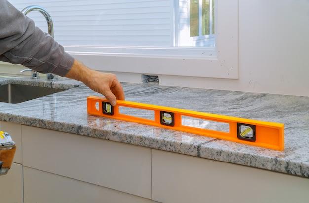 花崗岩のカウンタートップの改修と花崗岩のキッチンインテリアキャビネットとの取り付け Premium写真