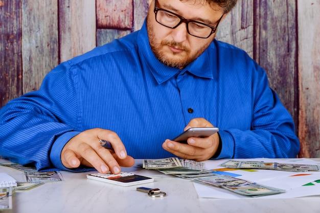 Местный бизнесмен с помощью калькулятора общей стоимости оплаченных долларовых купюр Premium Фотографии