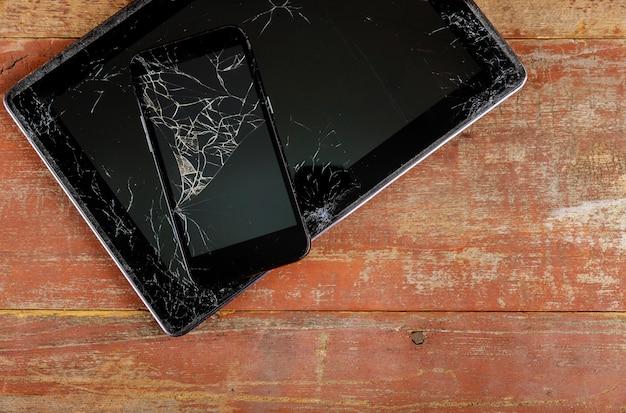 タブレットとスマートフォンの木製の背景に壊れたガラススクリーン Premium写真
