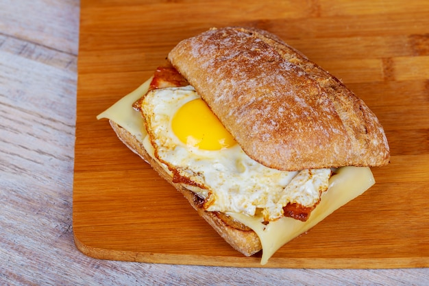 Гамбургер с беконом, яйцом и картофелем фри на деревянной разделочной доске. Premium Фотографии
