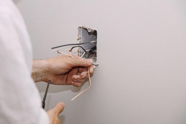 乾式壁に取り付けられた電線とコネクタを備えた未完成の電気主電源コンセント Premium写真