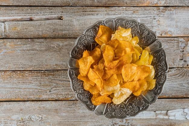 木の上の混合ポテトチップスの銀ボウル Premium写真